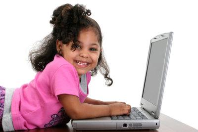 Three year old toddler girl in pink playing with a laptop computer