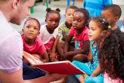 man teaching children in class